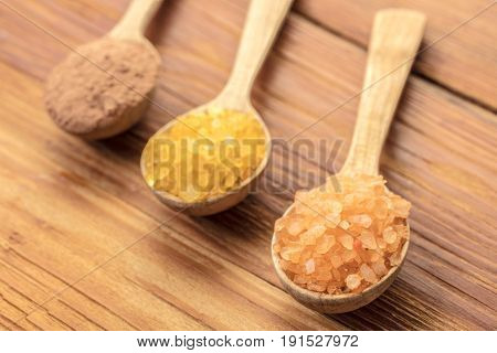 Spoons with phyto salt and clay on a wooden background