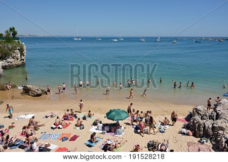 CASCAIS PORTUGAL - JUNE 07 2017: People sunbathing on the Praia da Rainha public beach. Cascais is famous and popular summer vacation spot for Portuguese and foreign tourists