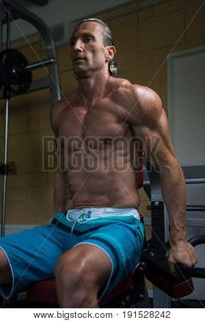 Muscular Man Exercising Triceps On Machine