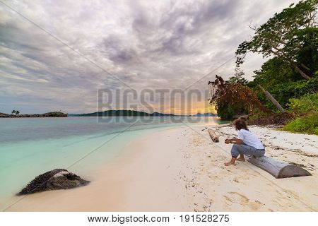 Tourist watching a relaxing sunset sitting on the beach in the remote Togean Islands Central Sulawesi Indonesia upgrowing travel destination in recent years. Wide angle view.