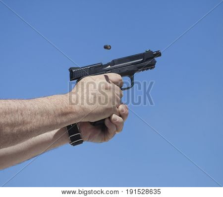 Empty brass leaving a semi auto handgun with sky behind