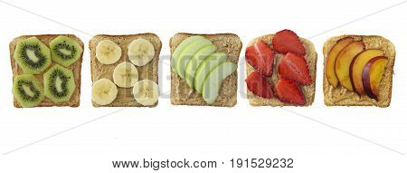 Sandwiches with peanut butter and fruits isolated on white background. Fresh healthy appetizer snack with bread. Sandwiches on bread topped with fresh strawberry banana apple nectarine and kiwi. Healthy breakfast with toasts. Top view.