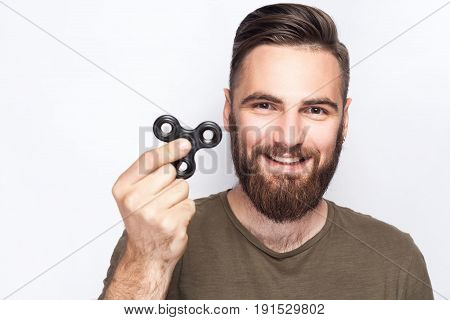 Young man holding and playing with fidget spinner. looking at camera. studio shot on white background.