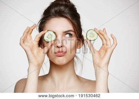 Young beautiful naked girl smiling hiding eye behind cucumber slice over white background. Beauty spa and cosmetology concept. Copy space.