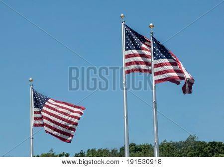 Three Wind Swept American Flags Flying On Flagpoles