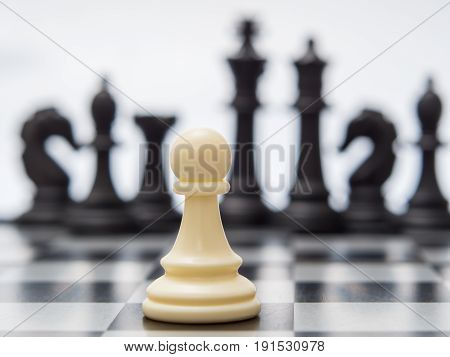 White Pawn Against The Background Of Dark Chess Pieces