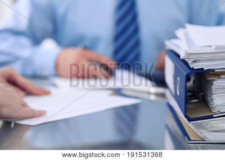 Binders with papers are waiting to be processed by bookkeepers back in blur. Accounting planning budget, audit, insurance and business concept.