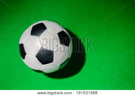 Top View Of Soccer Ball On Green Grass Background