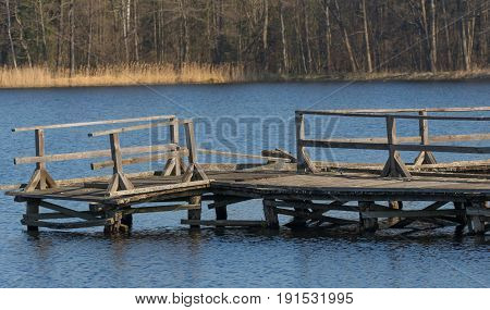 Old boardwalk for fishing almost destroyed in spring over calm water, Bialowieza Forest, Poland, Europe