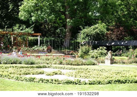 MAINZ, GERMANY - JUNE 10: Visitors of the Volksspark Mainz sit on park benches in the semi-shade of a garden area on June 10, 2017 in Mainz.