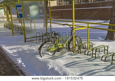 MOSCOW RUSSIA JANIARY 11 2017: Lonely bicycle left on all winter at the bicycle parking. Moscow near the entrance to the main building of Moscow State University.