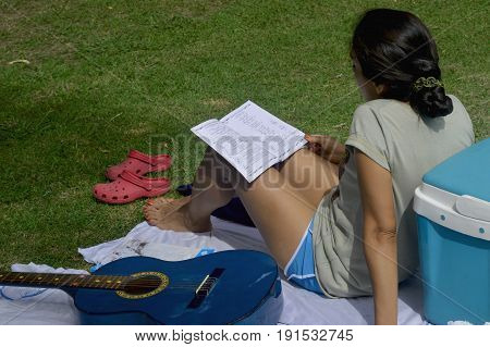 Relaxed woman rests at the campsite while studying a songbook