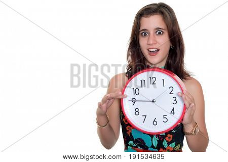 Beautiful teenage girl with a surprised expression showing the time on a big clock - Useful to illustrate lateness or the passing of time