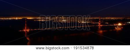 Golden Gate Bridge and the city of San Francisco from the Marin Headlands at night with reflections in the water