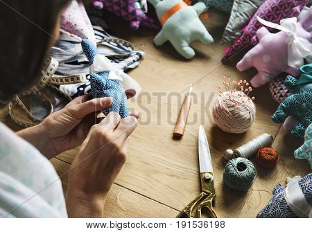 Closeup of hands sewing doll handicraft handmade