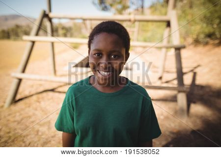 Portrait of smiling boy standing in boot camp during obstacle course