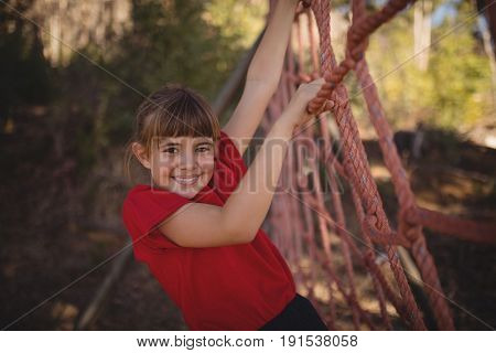 Portrait of happy girl climbing a net during obstacle course in boot camp