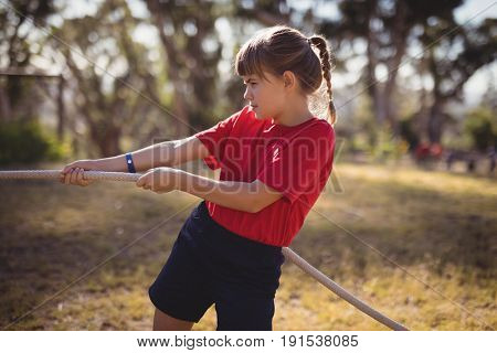 Determined girl practicing tug of war during obstacle course in boot camp