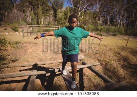 Boy walking on obstacle during obstacle course in boot camp