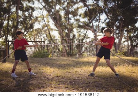 Determined kids practicing tug of war during obstacle course in boot camp