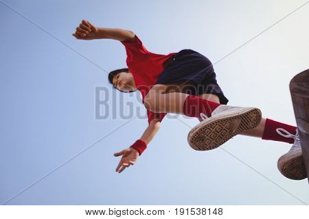 Determined boy jumping over obstacle in boot camp