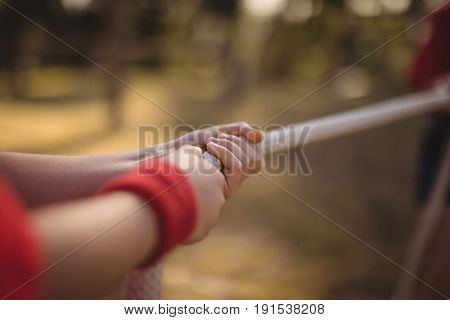 Hands of kid practicing tug of war during obstacle course in boot camp