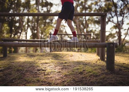 Low section of kid walking on obstacle during obstacle course in boot camp