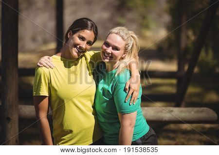 Portrait of happy friends standing with arms around during obstacle course in boot camp