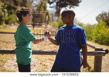 Happy friend holding hands during obstacle course in boot camp
