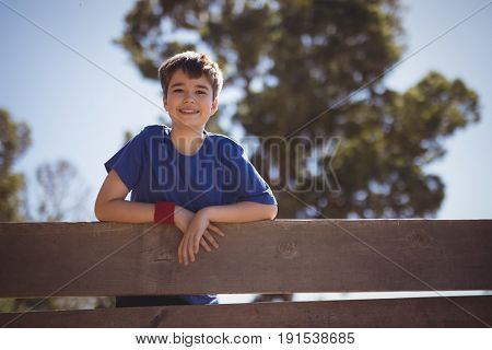 Portrait of happy boy standing on wooden wall during obstacle course in boot camp