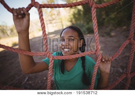 Portrait of happy girl standing near net during obstacle course in boot camp