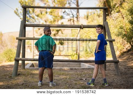 Portrait of happy boys standing with hands on hip during obstacle course in boot camp