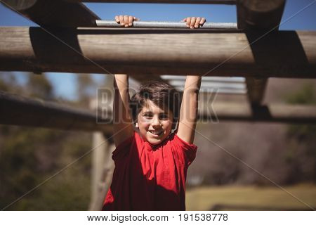 Portrait of happy boy exercising on monkey bar during obstacle course in boot camp