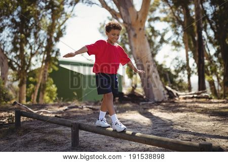 Happy boy exercising on obstacle during obstacle course in boot camp