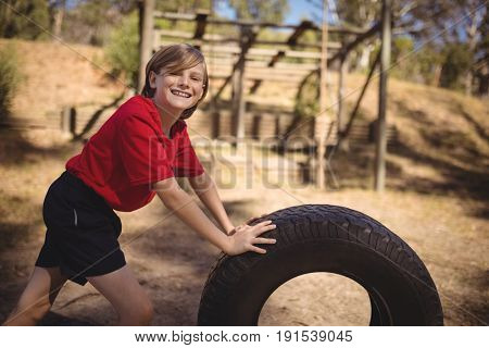 Portrait of smiling girl exercising with huge tyre during obstacle course in boot camp
