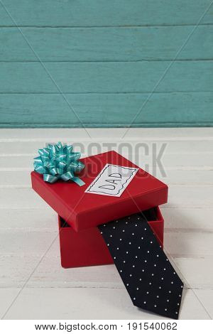 High angle view of necktie in gift box with dad text on table