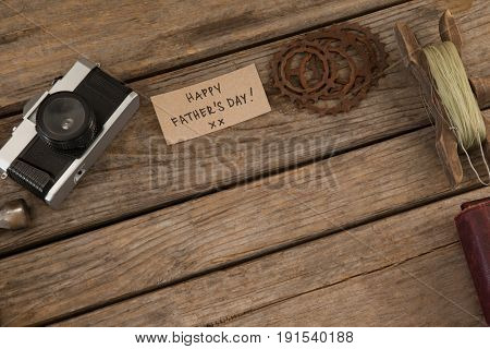 High angle view of paper with happy fathers day text by gears and camera on wooden table