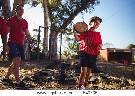 Trainer instructing a boy during obstacle course training in the boot camp