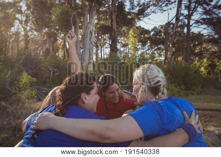 Group of fit women forming huddles in the boot camp on a sunny day