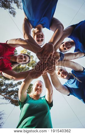 Portrait of fit womens group forming hand stack in the boot camp