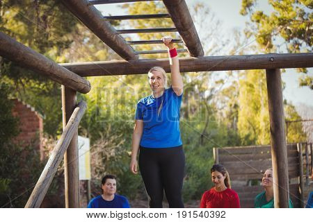 Woman ready to climb monkey bars during obstacle course training in the boot camp