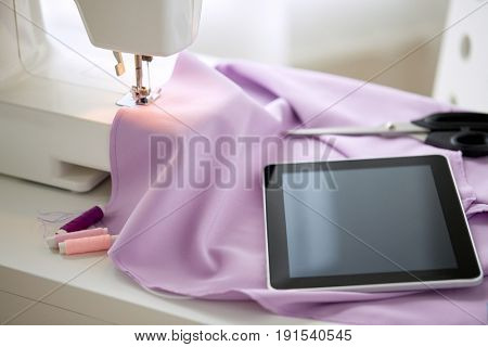 needlework, technology and tailoring concept - sewing machine with tablet pc computer, scissors, spools of thread and fabric