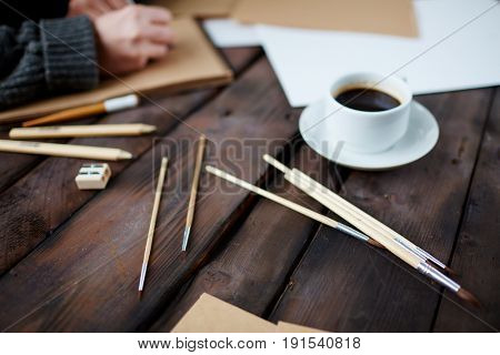 Painting supplies and cup of coffee on wooden table
