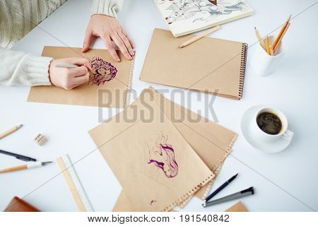 Hands of artist drawing pics of women by table