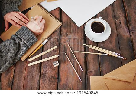 Human hands drawing in notepad with cup of drink and painting supplies near by