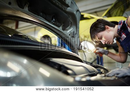 Car repair specialist with lamp inspecting engine