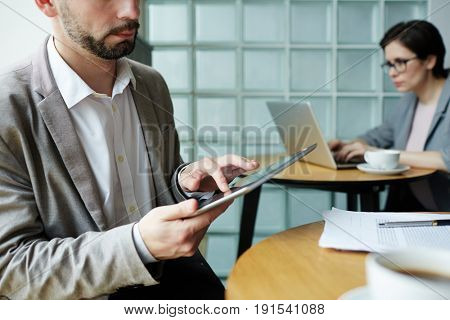 Closeup portrait of business people working at separate tables in co-working space, using portable computers