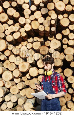 Engineer with papers and smartphone texting by stack of logs