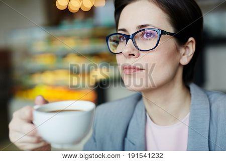 Portrait of confident modern businesswoman enjoying coffee break in bakery cafe