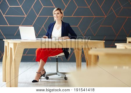 Successful newsreader looking at camera while browsing in the net